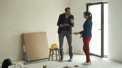 Couple with smartphone and tablet fighting about new home project Stock Footage