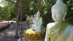 Caucasian woman walks along white Buddha statue gallery Stock Footage