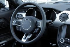 Dashboard and multifunction steering wheel in leather car interior - stock photo