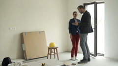 Couple with smartphone talking about new home project Stock Footage