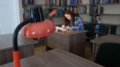 A student sits at a table in the library and writes in a notebook. 4K - stock footage