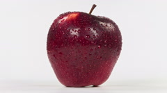 Wet red apple isolated on white background, close-up rotation. Stock Footage