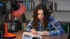 A student sits at a table in the library and writes in a notebook. 4K Stock Footage