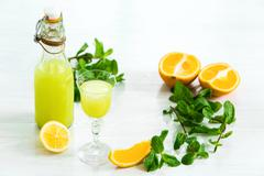 Home orange liquor in a glass and fresh oranges on the white wooden background - stock photo