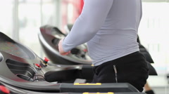 Man jogging and walking on treadmill, changing settings, finishing workout Stock Footage