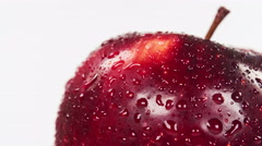 Wet red delicious apple isolated on white background, close-up rotation. Stock Footage
