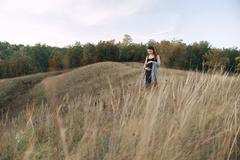 Pregnant woman in black dress and dreadlocks on the background of wild nature Stock Photos