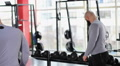 Male athlete exercising with heavy dumbbell in gym, looking at mirror reflection Footage
