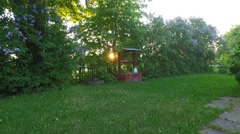 Sunset at old village. Slow motion. Old well. Green trees. Stock Footage