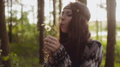 Stylish beautiful girl dressed in boho style blowing dandelions. Sun and rain - stock footage