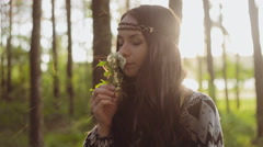 Stylish girl dressed in boho style smelling a flower in the forest. Sun and rain - stock footage