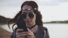 Stylish beautiful girl in sunglasses dressed in boho style with a smartphone Stock Footage