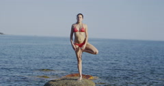 4K Beautiful woman doing yoga at the beach. Stock Footage