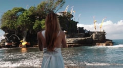 Woman tourist taking picture of Tanah Lot Stock Footage