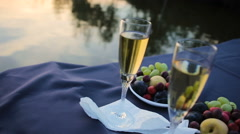 Two champagne glasses against a lake Stock Footage