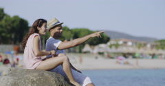4K Happy mixed ethnicity couple relaxing at the beach & throwing stones Stock Footage