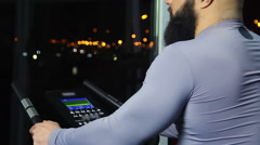 Bearded man looking at night cityscape through window after workout in gym Stock Footage