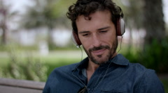 Expat man listening music on headphones at park. Stock Footage