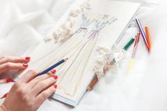 Talented dressmaker is designing bridal clothing - stock photo