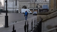Young woman walking along the South Bank of London with a backdrop of the Houses Stock Footage