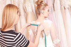 Talented female tailor is making bridal clothing - stock photo