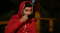 Young man in red clothes with a hood sits in a wooden arbor has tea at night and Stock Footage