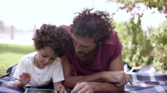 Father with son using digital tablet at park. Stock Footage