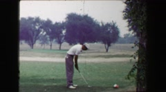 1968: Golfers tee off with iron club on par 3 hole as sweetheart girl watches. - stock footage