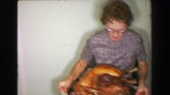 1957: Mother bringing out Thanksgiving turkey dinner father carving bird. Stock Footage