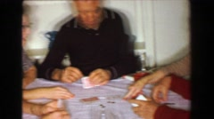 1957: Family playing poker cards after Thanksgiving dinner at kitchen table. - stock footage