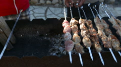 Camera moves from left to right and removes pork on skewers as it is fried in a - stock footage
