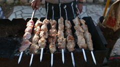 Camera moves from right to left and removes pork on skewers as it is fried in a - stock footage