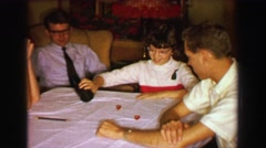 1957: Family playing dice rolling craps gambling game at den table. DAVENPORT, - stock footage