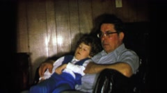 1957: Boy waking up in dad's lap confused as to where he is. DAVENPORT, IOWA Stock Footage
