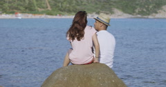 4K Happy mixed ethnicity couple kissing & embracing at the beach Stock Footage