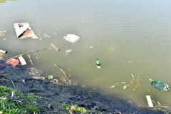 Rubbish, waste floating in polluted pond Stock Photos