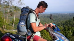 Happy Young Traveler with Backpack on Motorbike Enjoying Sea View Stock Footage