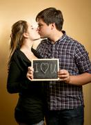 Couple kissing and and holding board with declaration of love Stock Photos
