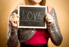 """Beautiful woman holding board with word """"Love"""" written by chalk Stock Photos"""