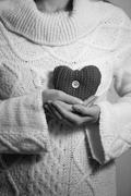 Monochrome photo of woman n sweater posing with decorative heart Stock Photos