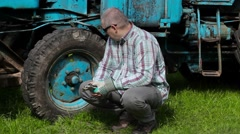 Worker with adjustable wrench thinking near tractor Stock Footage