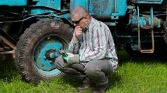 Worker looking to adjustable wrench and thinking near tractor - stock footage