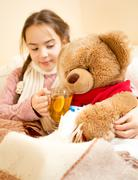 sick girl lying in bed and giving tea to teddy bear - stock photo