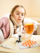 little girl with flu lying in bed and looking at cup of tea - stock photo