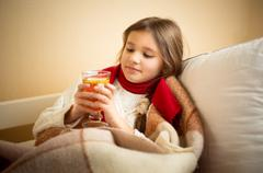 Cute girl got flu and holding cup of tea at bed Stock Photos