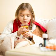 Little sick girl lying in bed and blowing on hot tea Stock Photos
