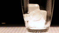 Into a glass with ice pour mineral water on a black background - stock footage
