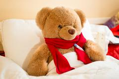 brown teddy bear in read scarf lying in bed with thermometer - stock photo