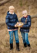Two girls on Easter egg hunt at forest Stock Photos