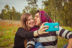 Couple doing silly  faces while taking selfie picture with their mobile phone Stock Photos
